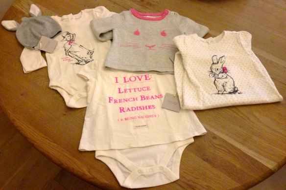 (L to R) Peter Rabbit Bunny Ears Hat; Puff Sleeve Bodysuit; Intarsia Rabbit Sweater; Short Sleeve Graphic Body Double; Peter Rabbit Graphic Footed One Piece