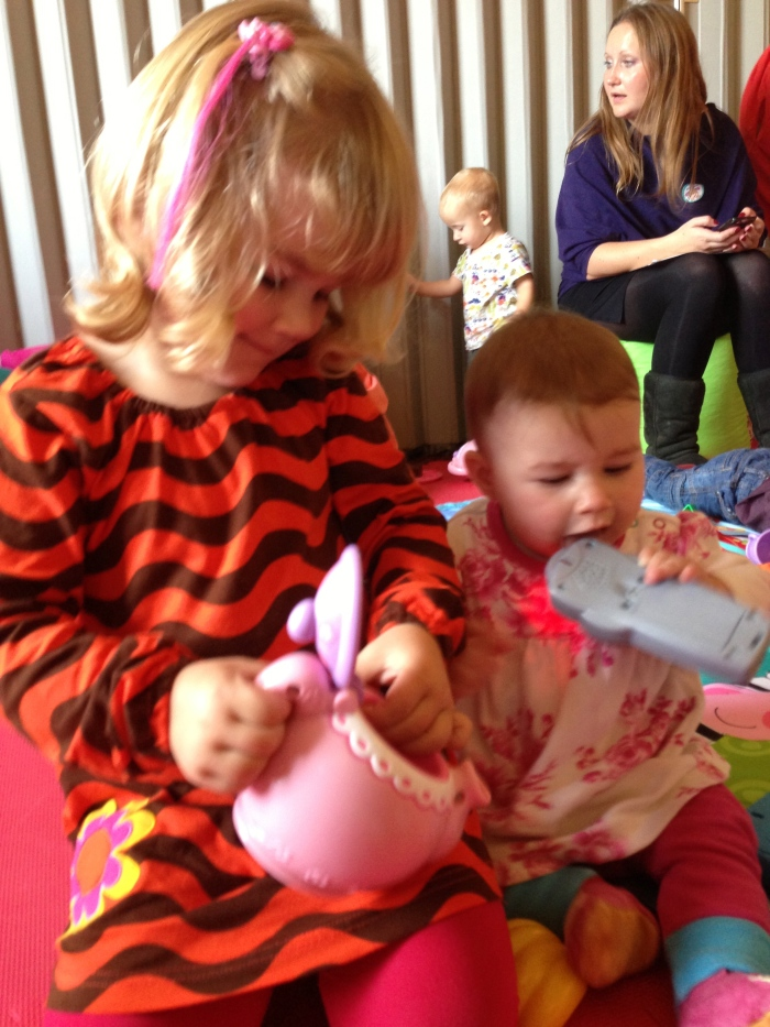 Allegra playing with the Fisher-Price Laugh & Learn Say Please Teaset and Claudia has a chew on the Click 'n' Learn Remote